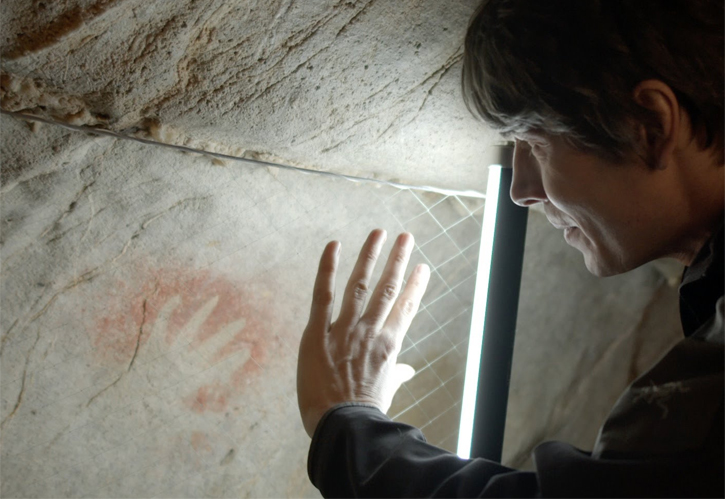 Brian Cox staring at a child's hand print made at least 35.000 years ago in Cantabria Cave, Spain.